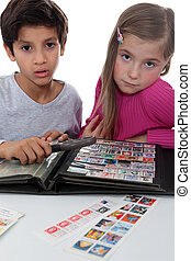 Two young children stamp collecting