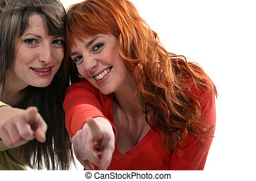 Two friends pointing at the camera.