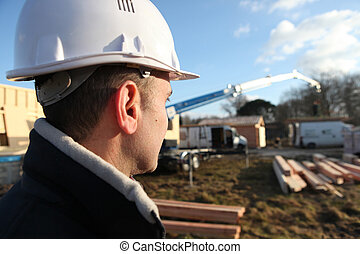 foreman in construction site with back turned to camera