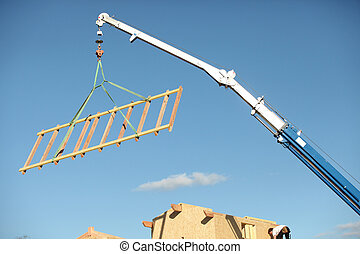 A crane lifting a wood structure.