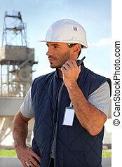 Foreman listening to radio receiver