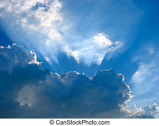 Blue sky with sun rays through the clouds