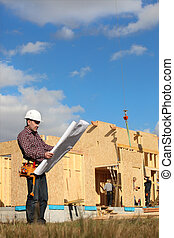 Foreman overlooking construction of wooden house