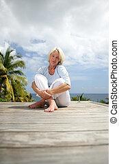 Senior woman sitting on a deck