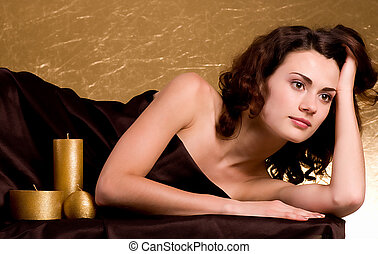 Spa woman with golden candles