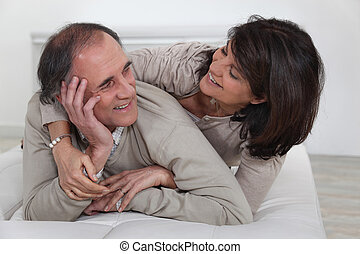 Middle-aged couple laying on bed