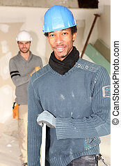 Construction workers carrying plasterboard