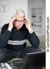 Stressed senior sat with laptop