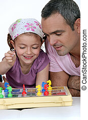 Little girl playing to a board game with man