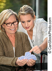 Grandmother and granddaughter playing cards