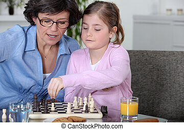 Mother teaching daughter how to play chess