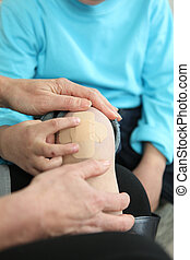 An adult putting a plaster on a child's knee