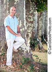 Grey-haired man leaning against tree