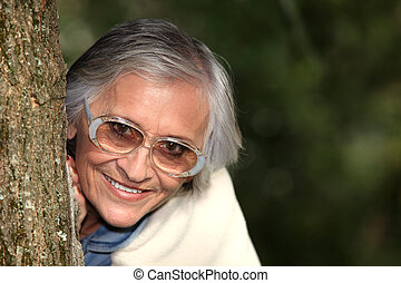 Elderly woman behind tree trunk