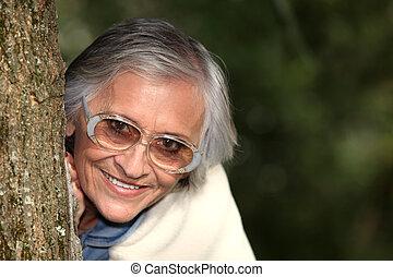 Elderly woman behind tree trunk