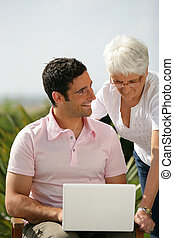 Man and senior woman with a laptop