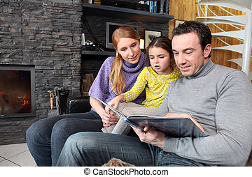 happy parents reading their young daughter a story