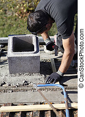Man adjusting cinder block placement