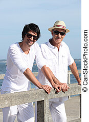 Father and son stood at the pier