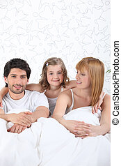 Parents and daughter in bed