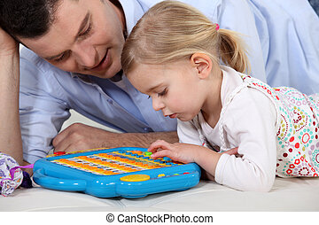Man playing a toy computer with a little girl