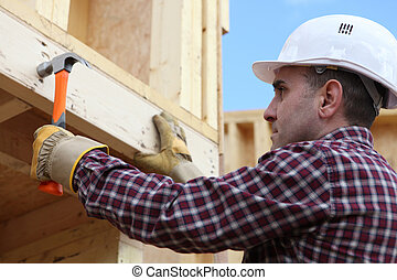 Worker nailing wooden framed house
