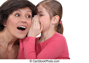 young daughter sharing secret with mom