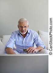Senior man using a credit card online