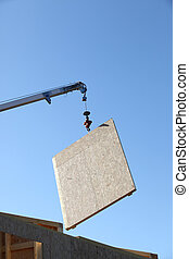 Wooden panel being lifted by crane