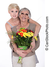 Daughter offering mother flowers