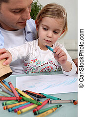 Man with little girl colouring