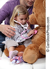 Young girl listening to her teddys heartbeat