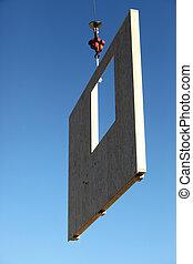 Crane lifting concrete wall