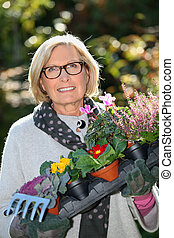 mature woman gardening and holding flowers