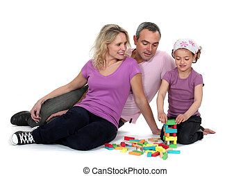 Parents watching their daughter play with blocks