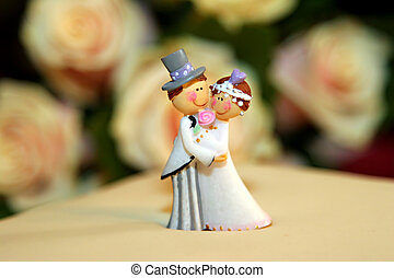 wedding cake dolls closeup with roses on background