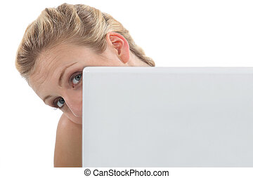 Woman peeking out from behind her laptop