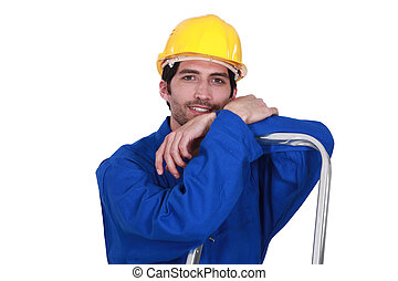 A construction worker resting on a ladder.