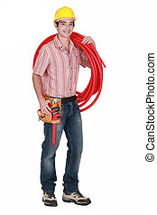 Young tradesman carrying corrugated tubing