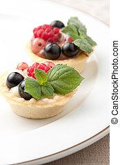 Indiviual freshly baked fruit tartlets with crisp golden...