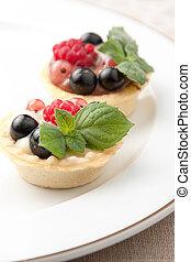 Indiviual freshly baked fruit tartlets with crisp golden...