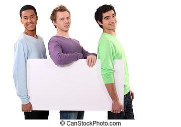 três, amigos, segurando, em branco, cartaz