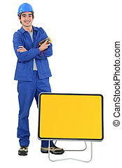 Tradesman standing in front of a traffic sign