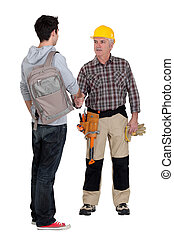 senior craftsman and young apprentice shaking hands