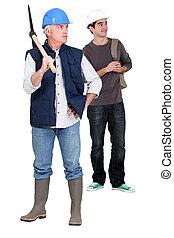 senior bricklayer and junior apprentice against studio background