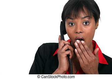 Afro-American woman talking on the phone and looking very...