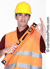 Man with spirit-level giving the ok sign