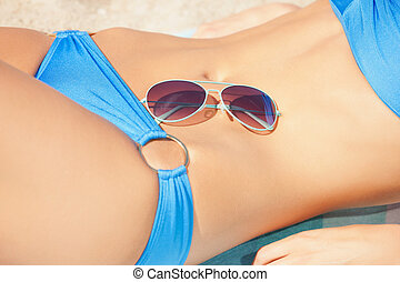 female belly, bikini and shades - closeup picture of female...