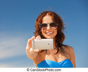 happy smiling woman using phone camera - picture of happy...