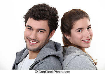 Portrait of a young man and woman standing back to back